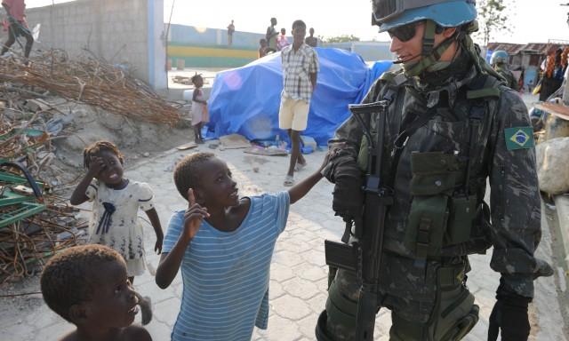 A peacekeeper supervises children in Haiti